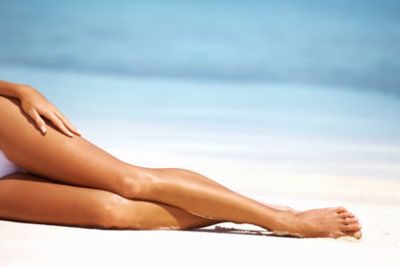 Glamorous woman with perfect legs relaxing on beach
